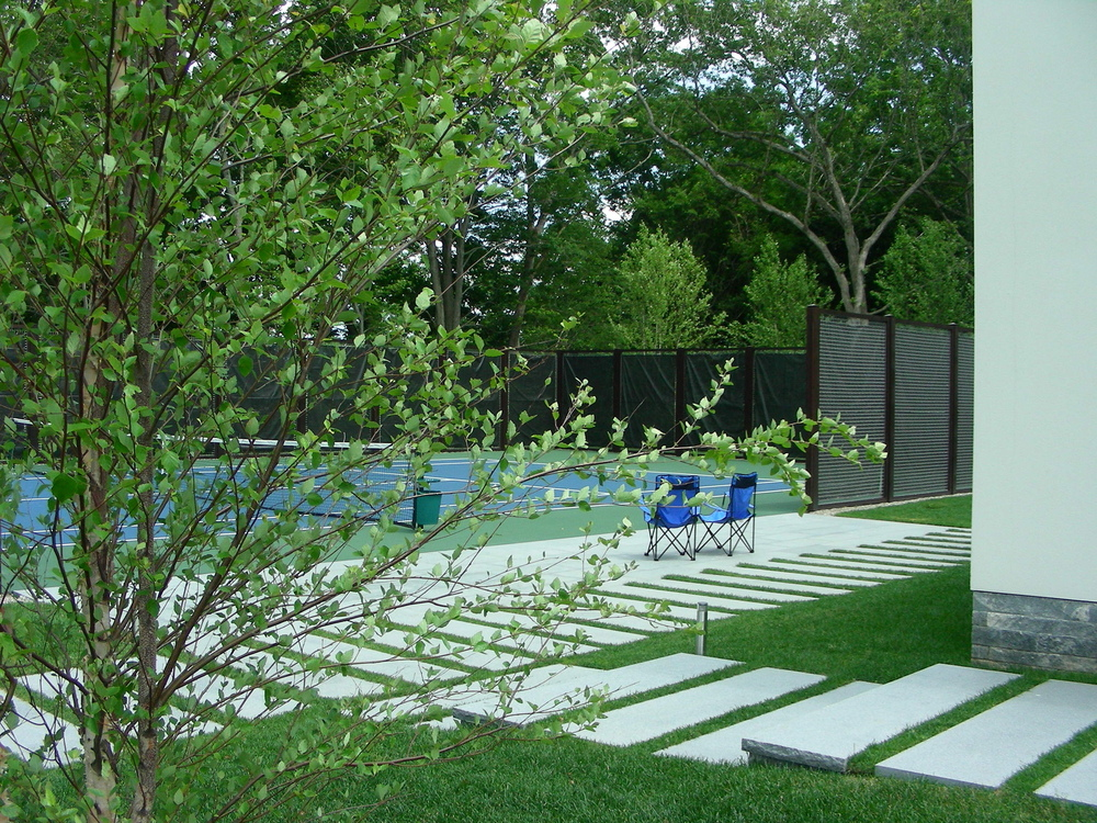 bkla studio - tennis court with stone path