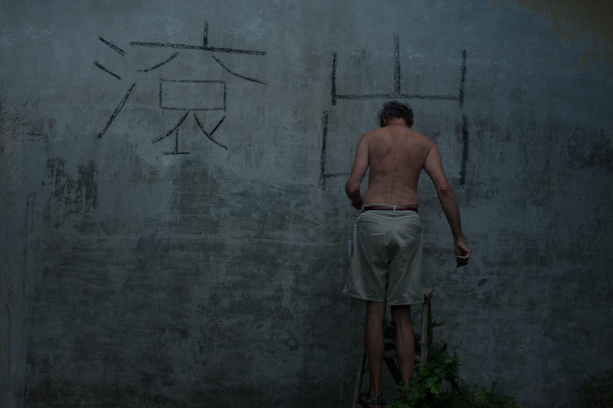 Adrienne Surprenant - Un habitant de Obra Juelo peint en madarin Dehors Chinois. Nombreux sont ceux qui ont affiché ces signes sur leurs maisons, pour protester contre la vente de leurs terres à une entreprise étrangère.