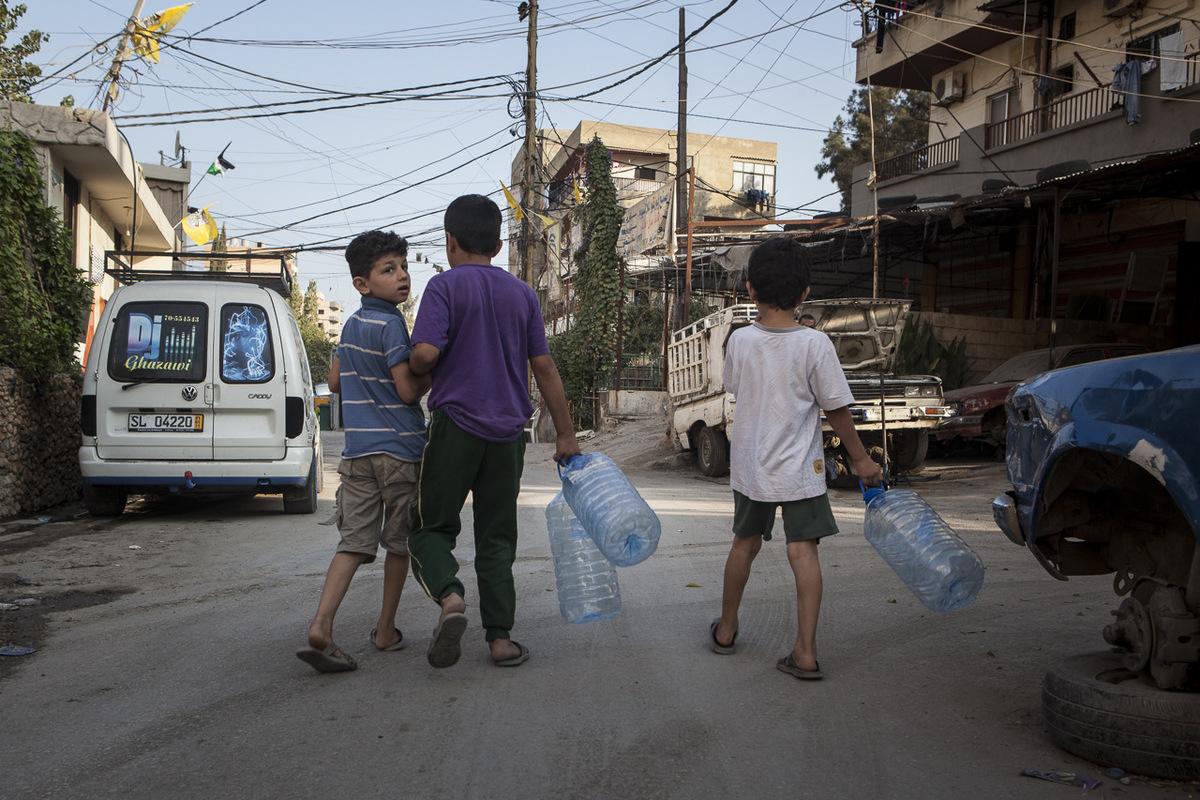 Adrienne Surprenant - Trois enfants syriens s'en vont remplir des galons d'eau à l'entrée du camp palestinien de Beddawi. Depuis le début de la guerre en Syrie, 1,2 millions de Syriens se sont joints aux plus de 400 000 réfugiés palestiniens qui vivaient déjà au Liban. Les réfugiés représentent aujourd'hui près d'un quart de la population du Liban, entrâinant des conditions de vie difficiles dans les camps surchargés.