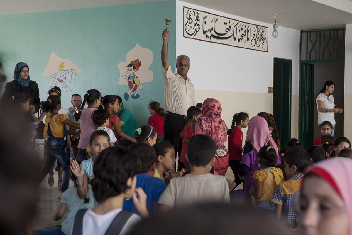 Adrienne Surprenant - Bassem Adres, directeur adjoint de l'école sonne la cloche. Il est originaire de Homs. Après la destruction de sa ville par le régime syrien, cet enseignant a trouvé refuge au Liban. A Ersal, ville frontalière avec la Syrie où plus de 120 000 Syriens ont trouvé refuge, il a enseigné dans les tentes-écoles des camps de réfugiés. En août 2014, Ersal a été le théâtre de violents combats entre l'Etat Islamique et l'armée libanaise. La guerre le poursuit. Désormais installé à Beddawi, il va prendre la tête de l'un des deux établissements scolaires de Tuyoor Al-Amal à la rentrée.