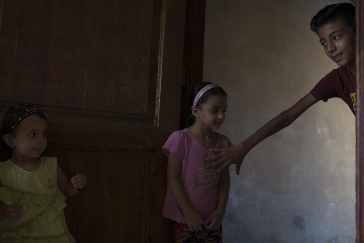 """Adrienne Surprenant - """"Je n'ai pas besoin de vérifier qu'ils apprennent"""", dit Mustafa à propos de ses nièces. """"Amani aide Sidra avec ses devoirs, laquelle surveille ceux d'Isra."""" Ici, Ayham Darwish, compagnon du neveu de Mustafa, leurs rend visite. A 12 ans, il prend soin des plus jeunes et assiste au désarroi des adultes: ingénieur en Syrie, son père travaille désormais dans un supermarché."""