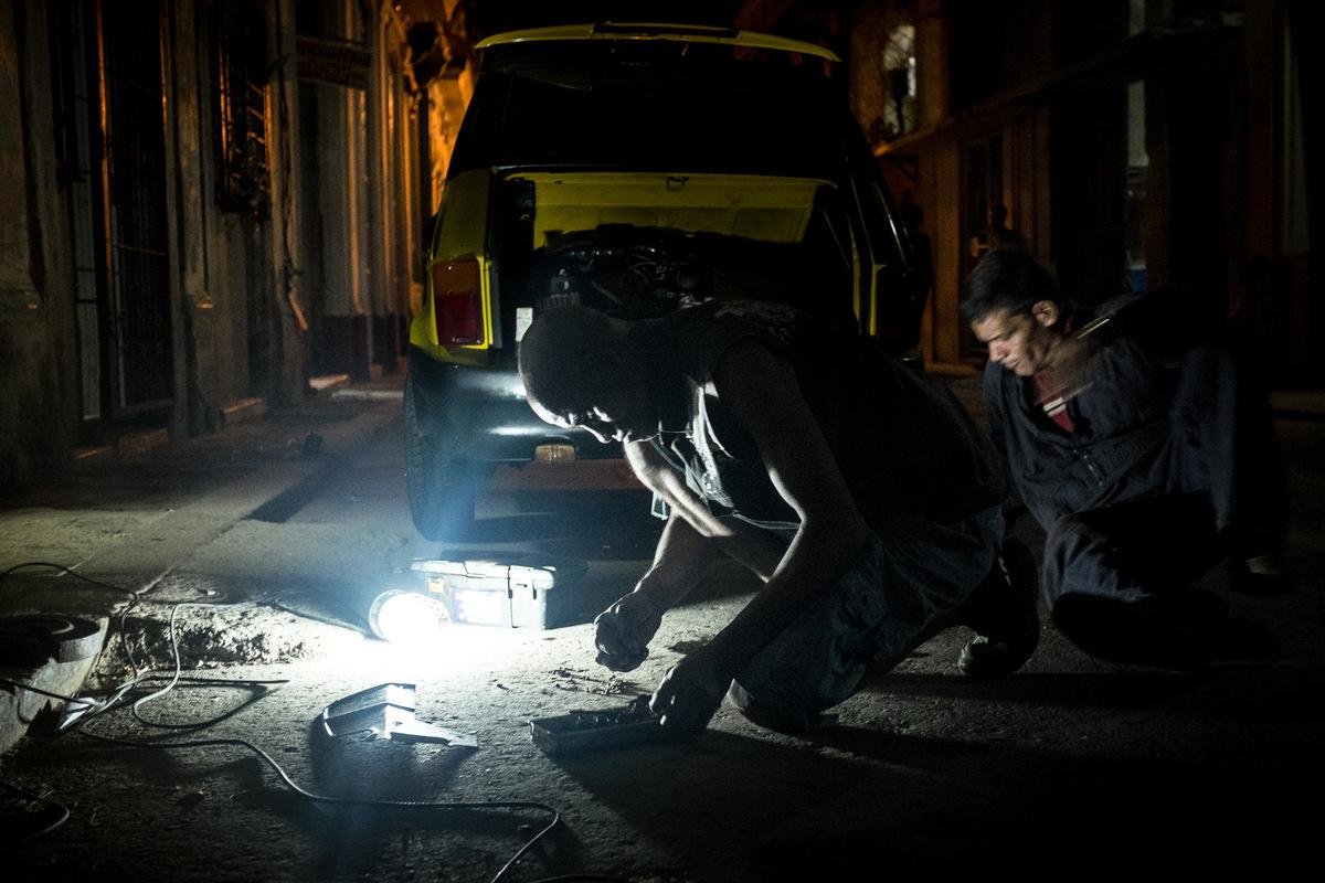 Adrienne Surprenant - Après la tombée de la nuit, deux hommes réparent une voiture, au centre de la Havane. La plupart des voitures sont composées de pièces dorigines différentes. La récupération, et la réutilisation font partie intégrante de léconomie, et du fonctionnement de la société cubaine.
