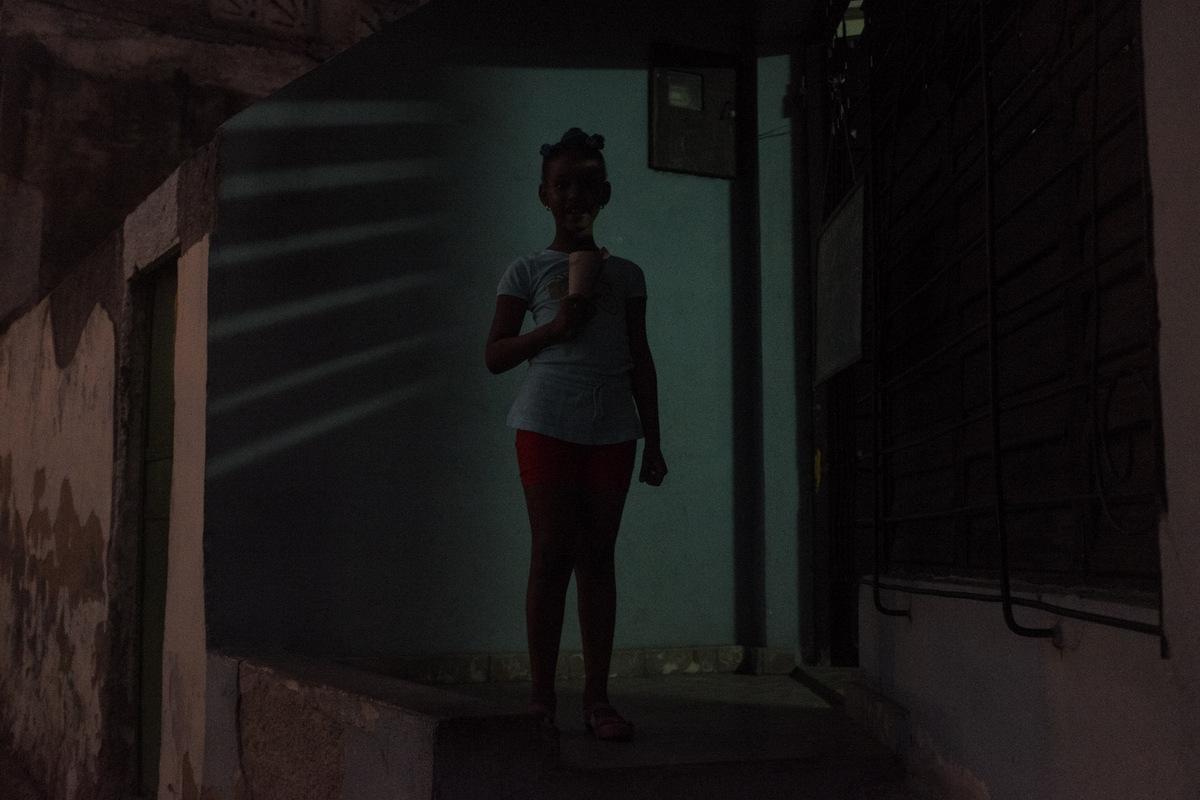 Adrienne Surprenant - Thalis, 7 ans, mange un dessert sur le pas de sa porte, à Santiago de Cuba.