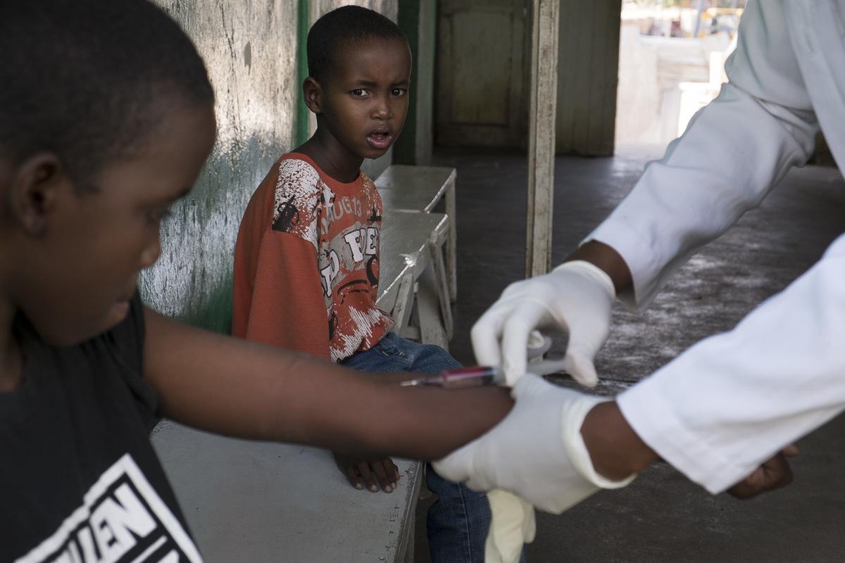 Adrienne Surprenant - Un enfant regarde son frère se faire prélever du sang, dans le hall dentrée de lhôpital.