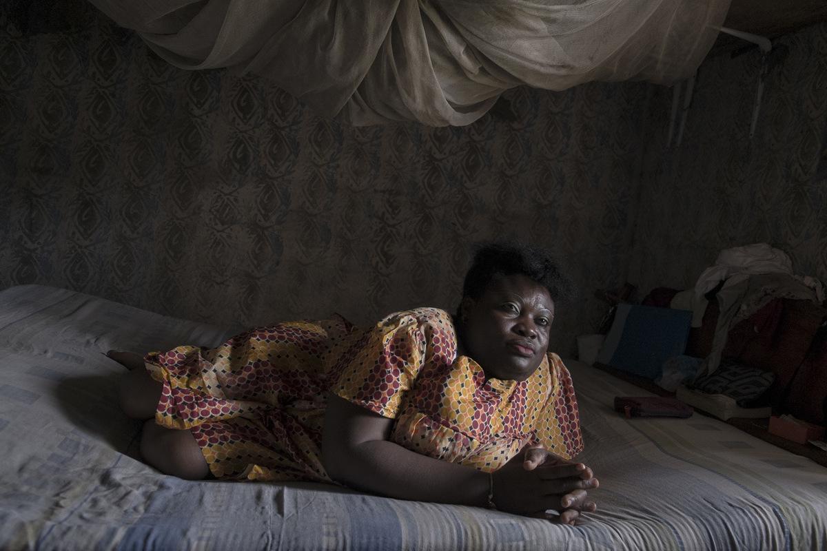 """Adrienne Surprenant - Hélène Ngo Honla, 42 ans, camerounaise Bassa. Elle est handicapée depuis l'âge de 5 ans, à cause de la poliomyélite. """"J'ai bien marché. Maman m'a dit que je partais souvent à l'aube, chercher l'eau que je mettais sur la tête. Maman me racontait ça. Elle est morte il y a dix ans. Je la pleure encore. Une mère ne peut jamais rejeter son enfant."""