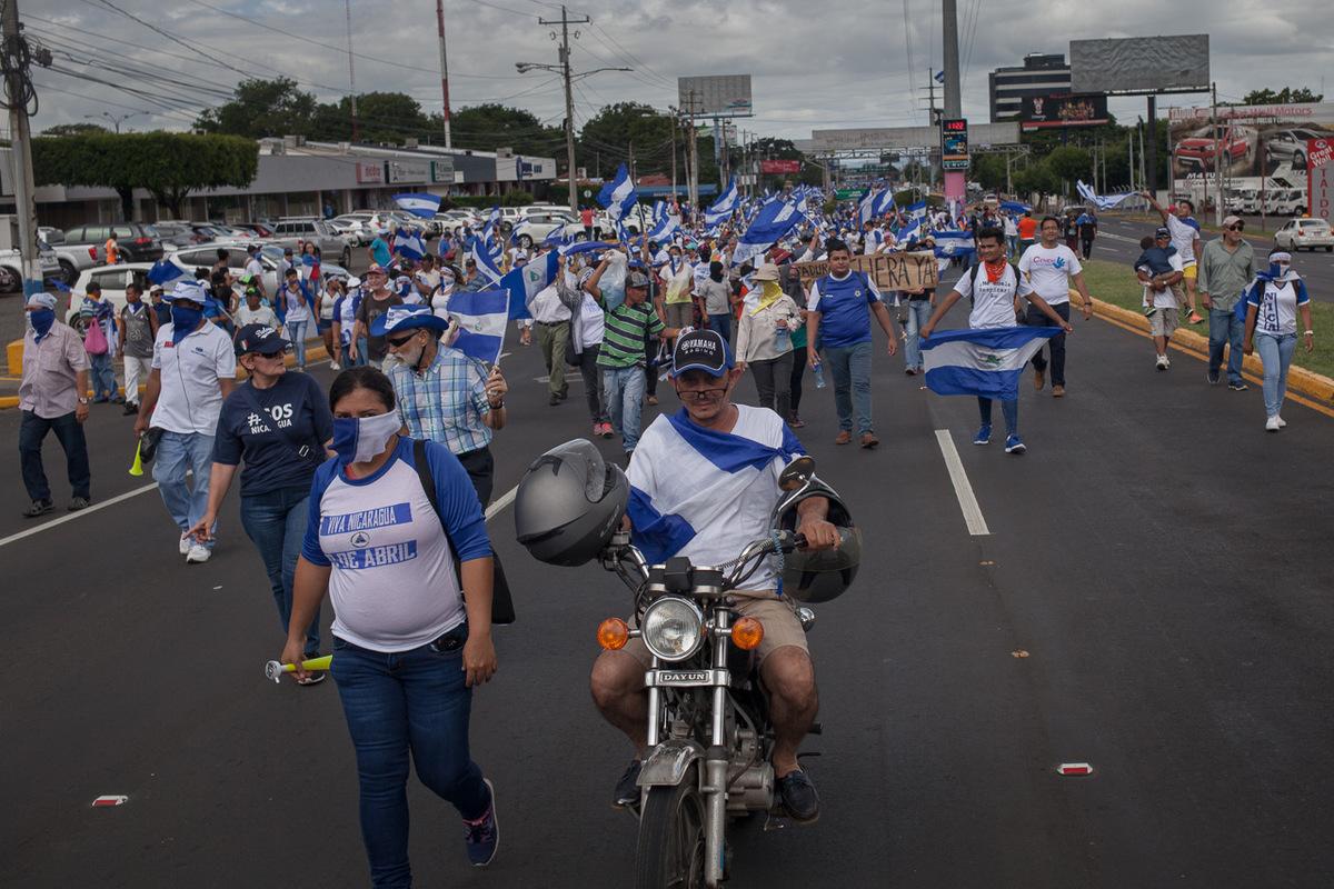 """Adrienne Surprenant - La """"Marche des drapeaux"""" du 2 septembre 2018 à Managua a commencé par un face à face entre manifestants contre le gouvernement et militants du parti au pouvoir, le FSLN. Puis, des centaines de personnes, criant """"nous n'avons plus peur"""" et """"qu'elle est la route? Que parte ce fils de pute!"""" ont défilé jusqu'à ce que d'une camionnette arborant le drapeau du FSLN, un tireur vise la foule."""