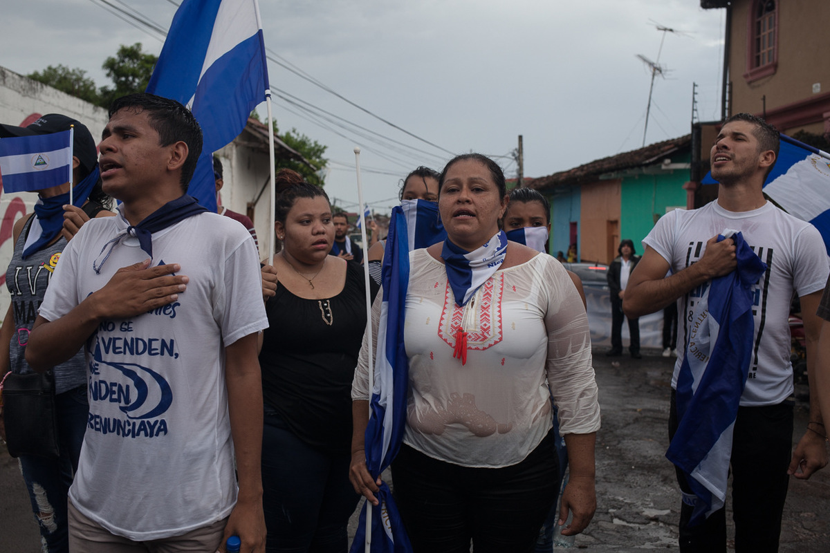 """Adrienne Surprenant - Olga P., 40 ans, chante l'hymne national à la fin d'une manifestation dans la ville de Granada. Ce jour-là, elle et sa fille ont posté des photos d'elles avec les leaders étudiants présents sur leur page Facebook. Cinq jours plus tard, à deux heures du matin, leur maison aurait été approchée par deux hommes en moto qui auraient lancé des pierres. Olga affirme avoir senti une odeur de gaz, et craint qu'ils n'enflamment sa maison. Le lendemain, munie d'une vidéo montrant les pierres autour de sa maison, elle est allée déposée une plainte au CPDH. """"Si il m'arrive quelque chose, je veux qu'on sache qui sont les coupables"""" dit-celle qui avait déjà été menacée sur Facebook deux fois par le passé, l'un des messages indiquant """"nous t'avons à l'oeil."""""""