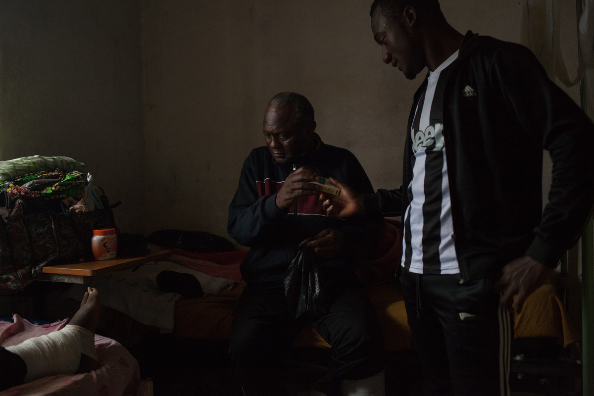 Adrienne Surprenant - Désiré Noutinou, 62, a merchant and father of 28 children, shows Dr Coveni his medicine. To stay at the hospital, he spends between 80,000 and 180,000 west african francs ($143-323) per month, according to patients. Desire complains about difficulty in feeding and taking care of his 28 children while he is at the hospital. He says he may have to leave when school starts, even if his wound is not healed, in order to go back to work so he can pay for his childrens schooling.