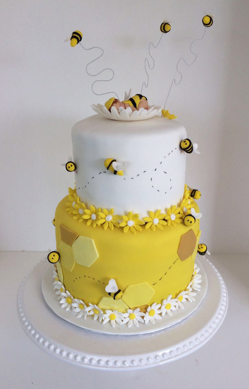 Simply Cakes - Bee themed baby shower cake topped with sleeping baby! Daisies around both tiers and buzzing bees to finish the look!