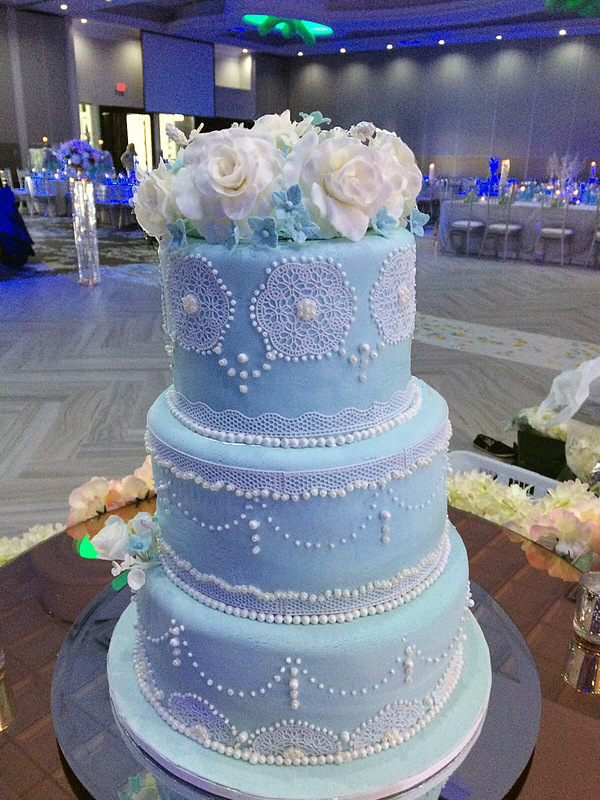 Simply Cakes - Elegant 3 tiered cake with delicate lace and pearl accents. Topped off with blue and white flowers!