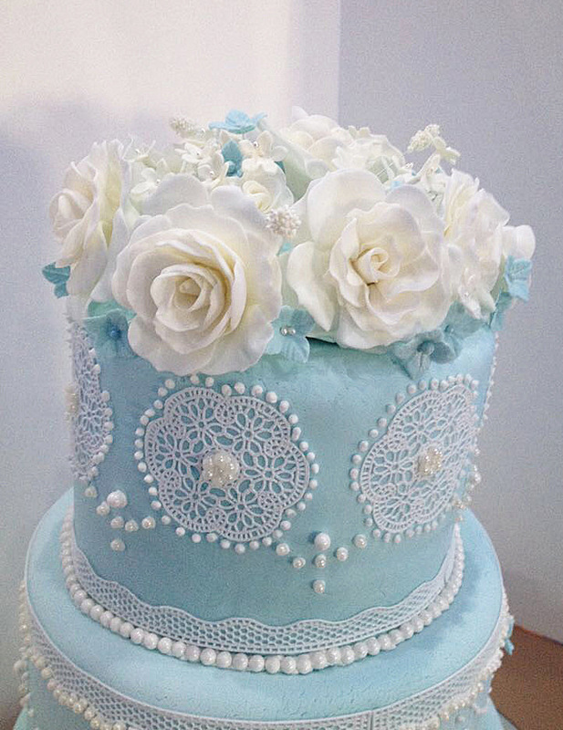 Simply Cakes - Cake topper with hand made fondant flowers to accent this blue and white lace cake!