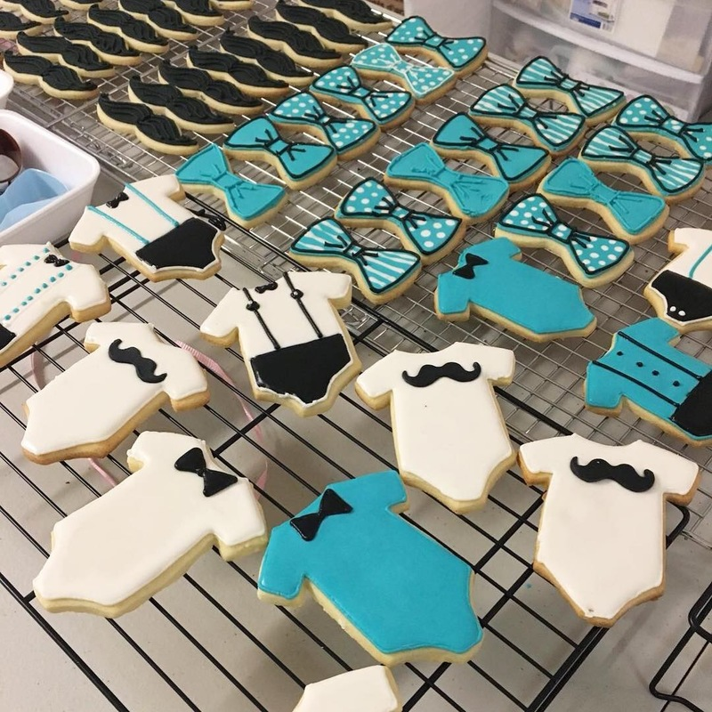 Simply Cakes - Blue and white onesie cookies with mustache accents