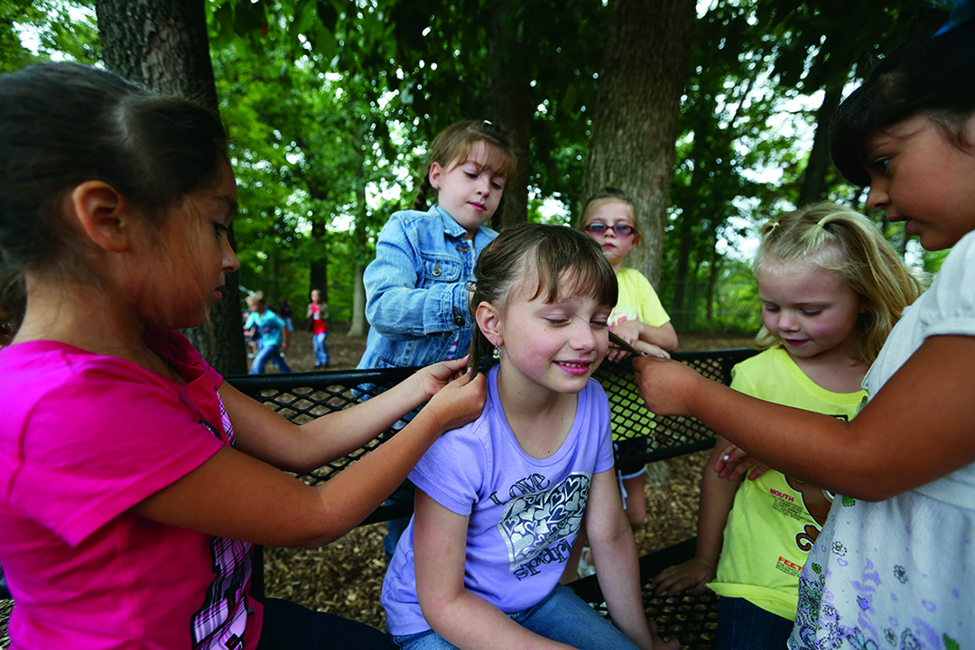 Jennifer Gonzalez | Multimedia Photojournalist - Mia Jimenz, 6, Kaylie Springston, 7, Amanda Kennon, 7, Chloe Miller, 7, and Lizette Rodriguez, 6 gather around Liberty McCormick, 6, to braid sections of her hair during recess.
