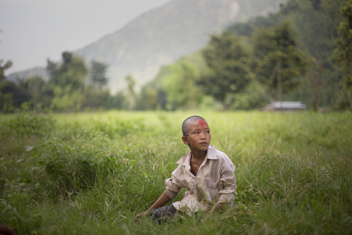 Jennifer Gonzalez | Multimedia Photojournalist - A boy sits in a field in the mountain town of Simli, Nepal. Simli will be one of the first towns submerged by water if the high dam is built. Nepal, 2013.